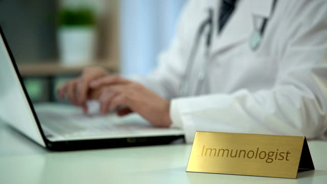 Male immunologist typing on laptop in office, working on medical reports video