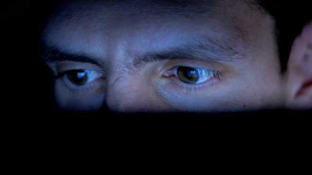 Male in Hat Looks at a Laptop Monitor at Night