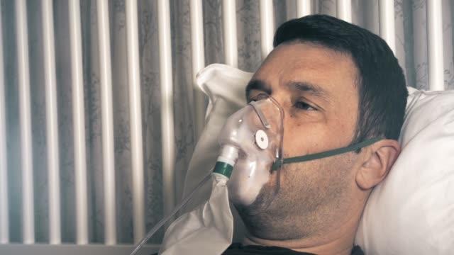 ein männchen in seinen 40er jahren erholt sich zu hause vom coronavirus. er trägt eine sauerstoffmaske wegen atembeschwerden. konzept-schuss. - sauerstoff stock-videos und b-roll-filmmaterial