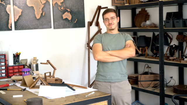 Male in his design studio, looking and smiling at camera. video