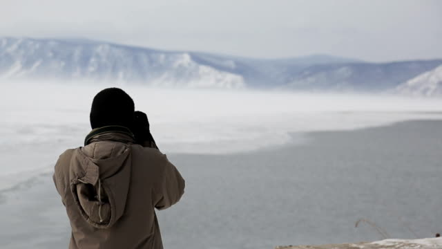 Male Indian tourist shoots snow-capped mountains on lake video
