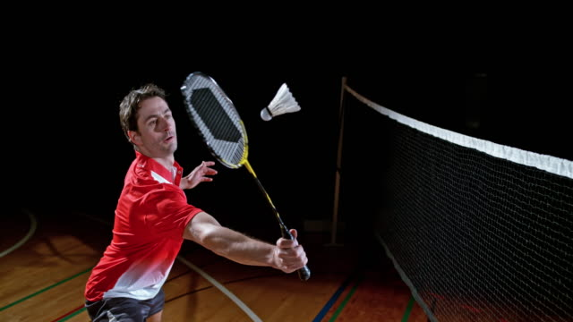 slo mo male indoor badminton player hitting a shuttlecock - badminton stock videos & royalty-free footage
