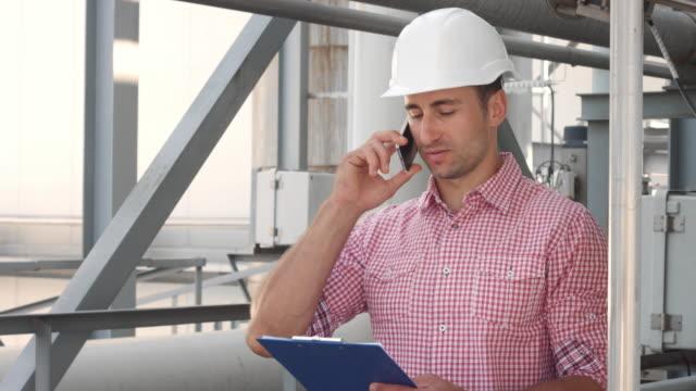 Male industrial engineer speaking phone on factory background video