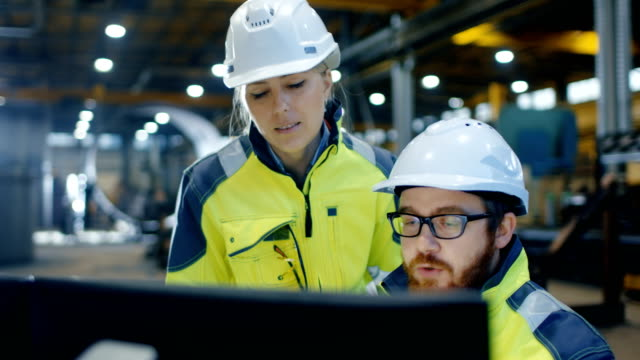 male industrial engineer works on the personal computer while female manager talks about project details. they work in heavy industry manufacturing factory. - metallurgia video stock e b–roll