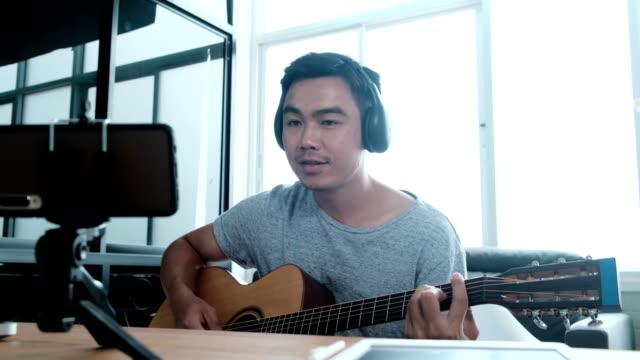 Male influencer playing guitar while making video tutorial,Vlogger recording guitar lesson on video camera