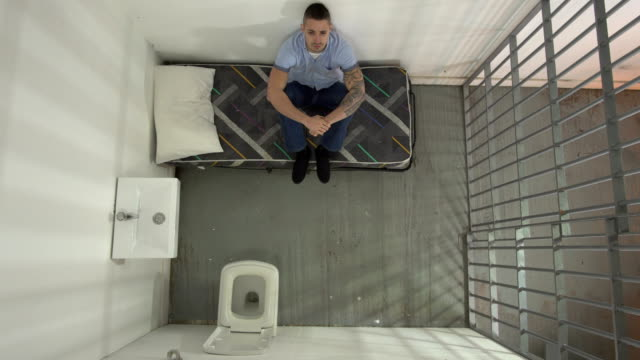 4K AERIAL: Male Inmate in Jail Cell sat on bed - vídeo