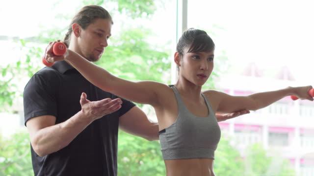 vídeos de stock, filmes e b-roll de instrutor e cliente masculinos que exercitam em casa - personal trainer