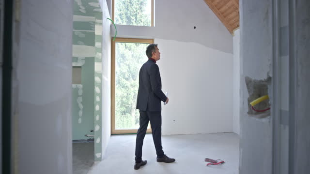 Male interior architect standing in the unfinished room and looking at the plans