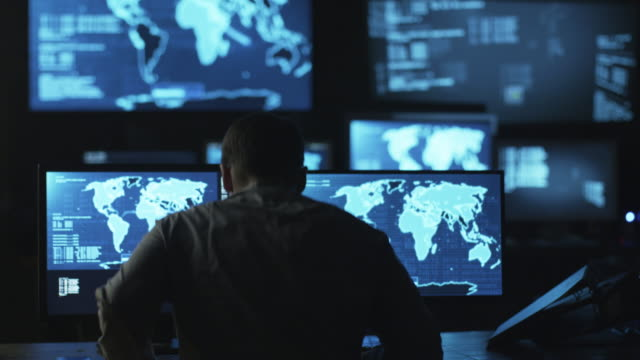 Male IT employee comes to monitoring room to work on computer with maps and data on display in a dark office room. video