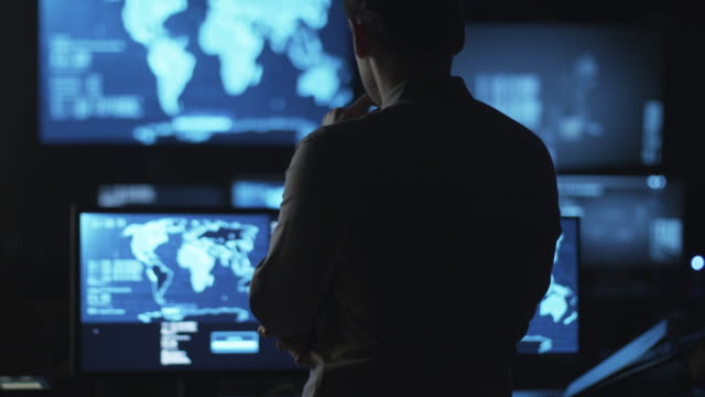Male IT employee is looking at computer screens with maps and data on display in a dark office room. video