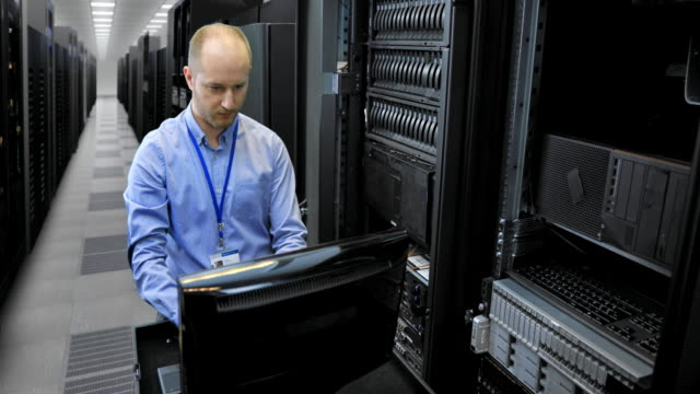 LD Male IT technician working on a omputer in the server room