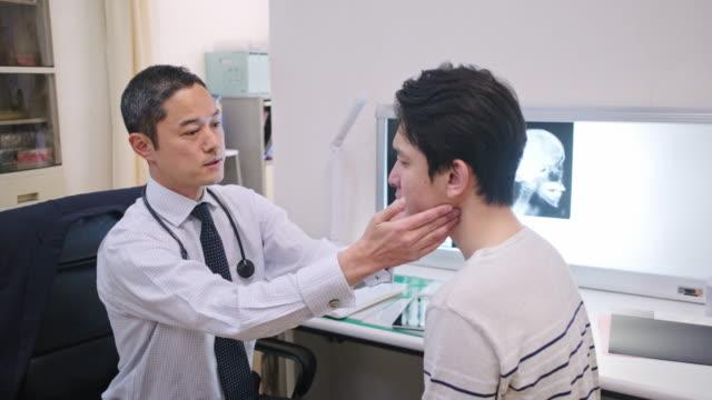 manlig japansk läkare undersöker ung patient på sjukhus - fysiotherapy bildbanksvideor och videomaterial från bakom kulisserna