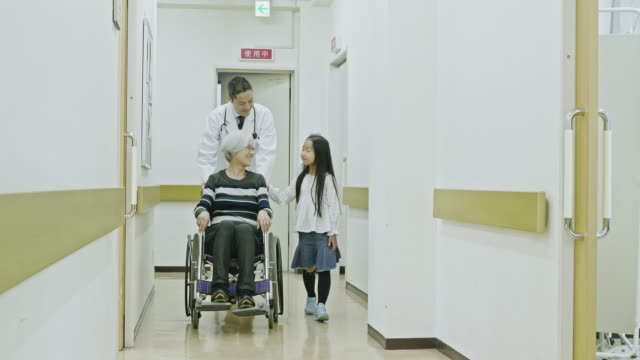 male japanese doctor pushing patient in wheelchair - nonna e nipote camminare video stock e b–roll
