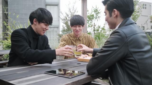 männliche japanische freunde genießen tee im dachgarten - grüner tee stock-videos und b-roll-filmmaterial