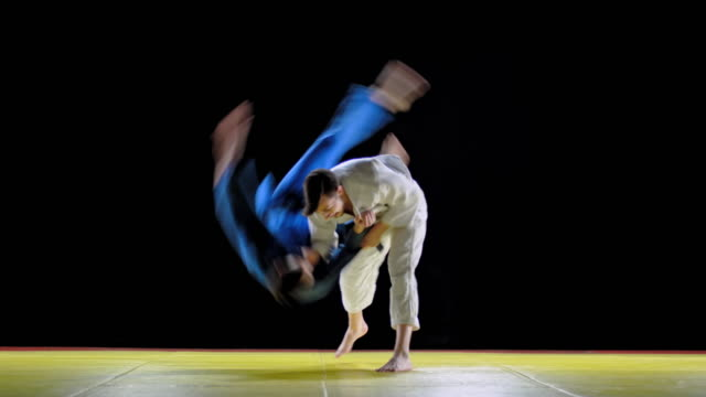 LD Male judoist in white outfit throwing his opponent on the floor Wide locked down shot of a male judoka in white outfit throwing his opponent on the tatami and holding him with his legs. Shot in Slovenia. martial arts stock videos & royalty-free footage