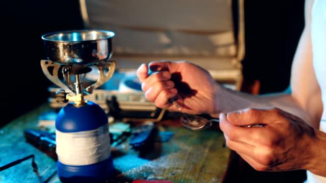 stockvideo's en b-roll-footage met junkie mannenhand heroïne dosis voorbereiden met behulp van lepel en sigarettenaansteker voor het smelten, spuit voor injectie. - amfetamine
