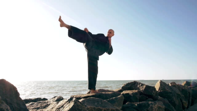 male karate fighter posing on stones sea background, slow motion video