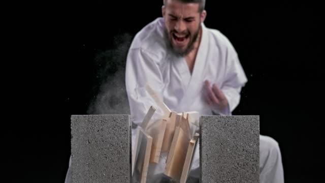 slo mo speed ramp ld 男性空手家がナイフの手で3枚の木製ボードを壊す - 空手点の映像素材/bロール
