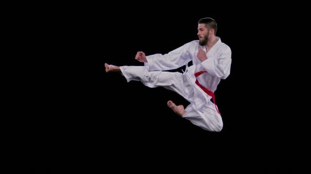 slo mo hız rampa erkek karateist uçan bir yan tekme yapıyor - karate stok videoları ve detay görüntü çekimi