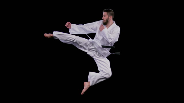 SLO MO LD Male karateist jumping into a flying side kick Slow motion wide locked down side shot of a male karateist jumping and doing a flying side kick. Shot on black background.  Shot in Slovenia. martial arts stock videos & royalty-free footage
