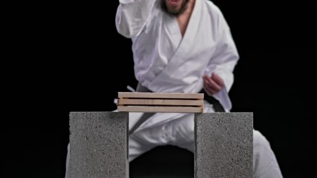 vídeos y material grabado en eventos de stock de slo mo ld karateka macho rompiendo tres tablas de madera con un movimiento de golpe de mano de cuchillo - kárate
