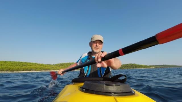 LD Male kayaker paddling a yellow sea kayak in sunshine