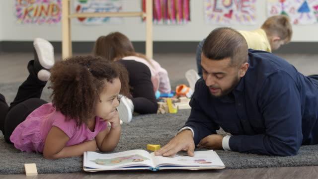 vidéos et rushes de un enseignant masculin de maternelle engagé avec une jeune fille - enfant d'âge pré scolaire