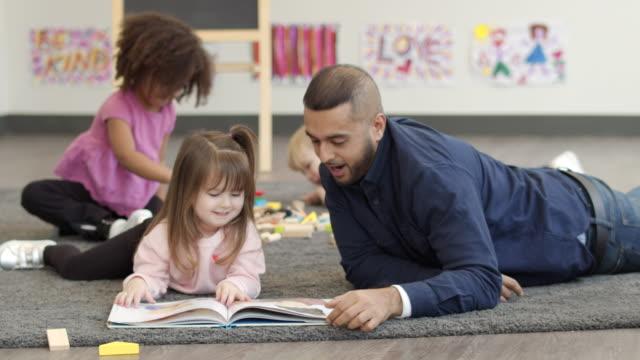 Male kindergarten teacher reading book to student