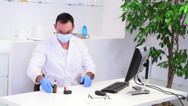 vídeos de stock, filmes e b-roll de trabalhador de laboratório masculino em um revestimento branco em sua mesa - pré estreia