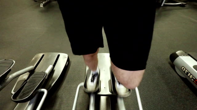 A male legs on an elliptical trainer in a gym video
