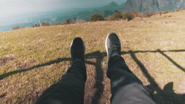 męskie nogi z czarno-białymi trampkami na huśtawce góry - ekoturystyka filmów i materiałów b-roll
