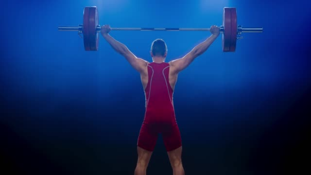LD Male lifter in red outfit lifting the barbell with the snatch lift