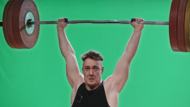 SLO MO TU Male lifter raising the barbell above his head