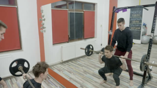 Male lifting weights and doing squats to work out his body muscles in gym with the help of a personal trainer video