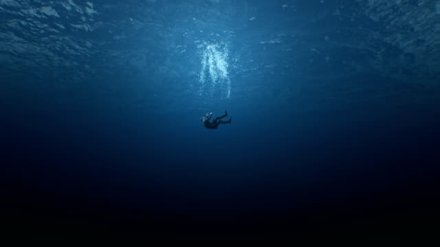 Male man businessman falls into the ocean and drowns. The concept of finance problems depression midlife crisis. Problems in personal life, credit slavery, debts mortgages. Symbol of abstract problems