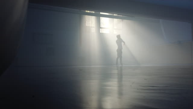 male man making excersice in a gym down a beam of light