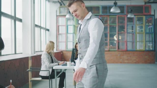 男性のマネージャーがオフィスを回り、同僚に歩み、机に向かって座り、書類を見てから捨てる。同僚が怒っている。コワーキング。オフィスライフ。競合 ビデオ