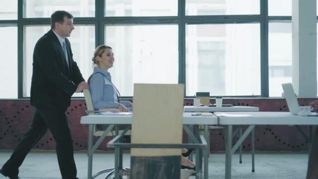 男性マネージャーがオフィスの椅子に女性の同僚を転がし、彼らは楽しんでいます。同僚に手を振る従業員。ロフトスタイルでコワーキング。オフィスライフ。お 祝い ビデオ