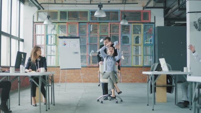 Eine männliche Managerin rollt eine Kollegin auf einen Bürostuhl, und sie wirft Geld um das Büro. Das Personal hat Spaß. Business-Interieur im Loft-Stil. Büroleben. Feier – Video
