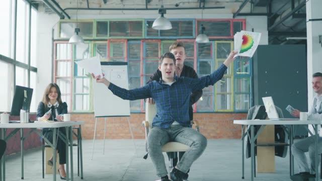 Ein männlicher Manager rollt seinen Kollegen in einen Bürostuhl und sie haben Spaß. Ein Mitarbeiter wirft Dokumente auf. Co-Working im Loft-Stil. Büroleben. Feier – Video