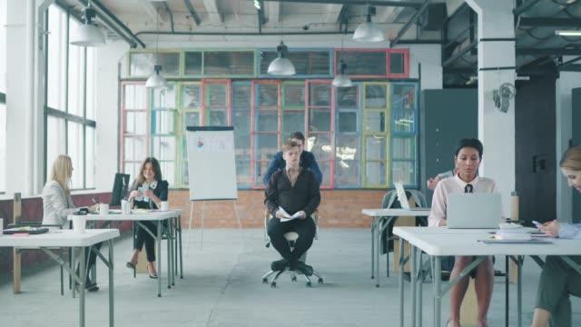 男性マネージャーが同僚をオフィスの椅子に座り、楽しんでいます。従業員が書類を投げる。ロフトスタイルでコワーキング。クリエイティブなオフィスライフ。お 祝い ビデオ