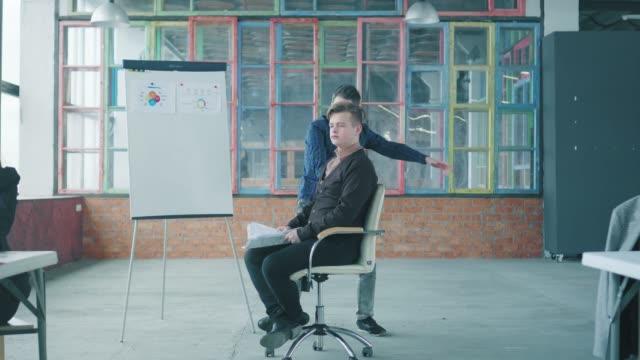 男性マネージャーがオフィスの椅子で同僚を振り回し、楽しんでいます。ロフトスタイルのオフィススペース。ビジネスライフ。コワーキング ビデオ
