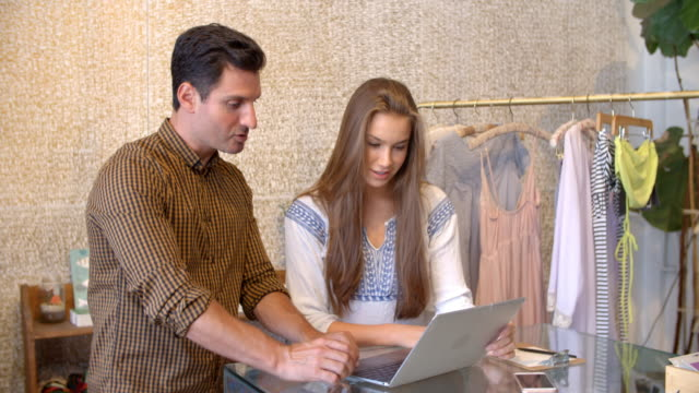 Male manager trains young woman using laptop in clothes shop video