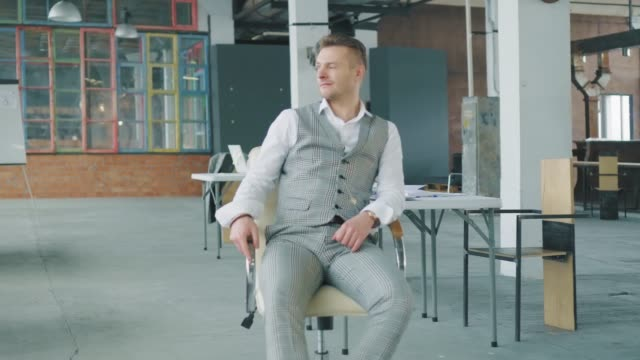 Ein männlicher Manager schaltet einen Bürostuhl zu einer Kollegin ein, zwinkert und flirtet mit ihr. Business-Interieur im Loft-Stil. Büroleben – Video