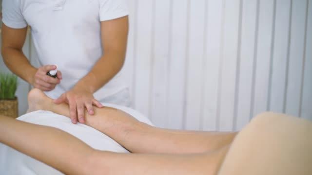 manlig massör massera vacker ung kvinna benet på bordet i spasalong. - massageterapeut bildbanksvideor och videomaterial från bakom kulisserna