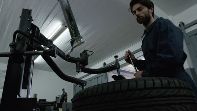 Male mechanic fixing a punctured tire at a garage looking focused