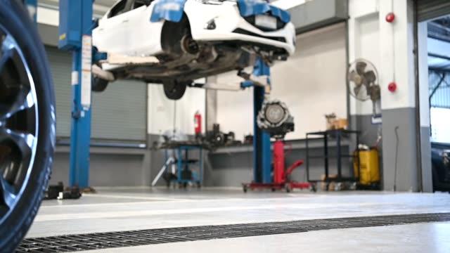 男性の整備士は、修理サービスガレージの背景でタイヤを保持し、ローリング。安全ロードトリップのための冬と夏のタイヤを交換する技術者の男。輸送・自動車メンテナンスコンセプト - 機械工点の映像素材/bロール