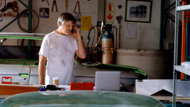Männliche Mechaniker telefonieren mit Handy 4k – Video