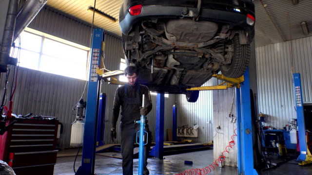 male mechanic using hydraulic lifter to lift car part. video