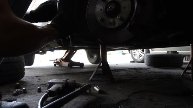 male mechanic working in auto repair shop, slow motion - klucz ręczne narzędzie filmów i materiałów b-roll